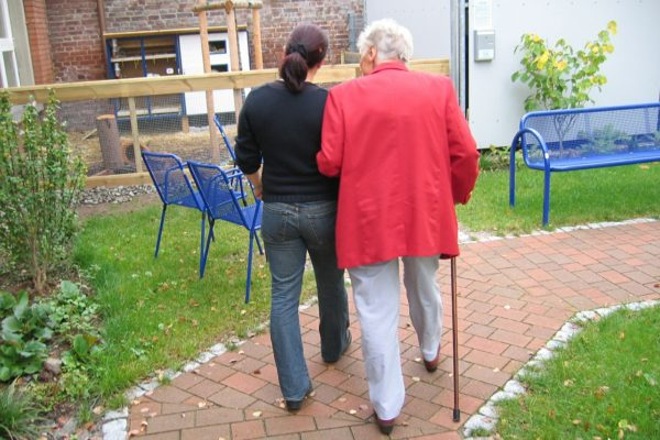 Younger person helping older person walking