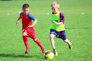2 kids playing football